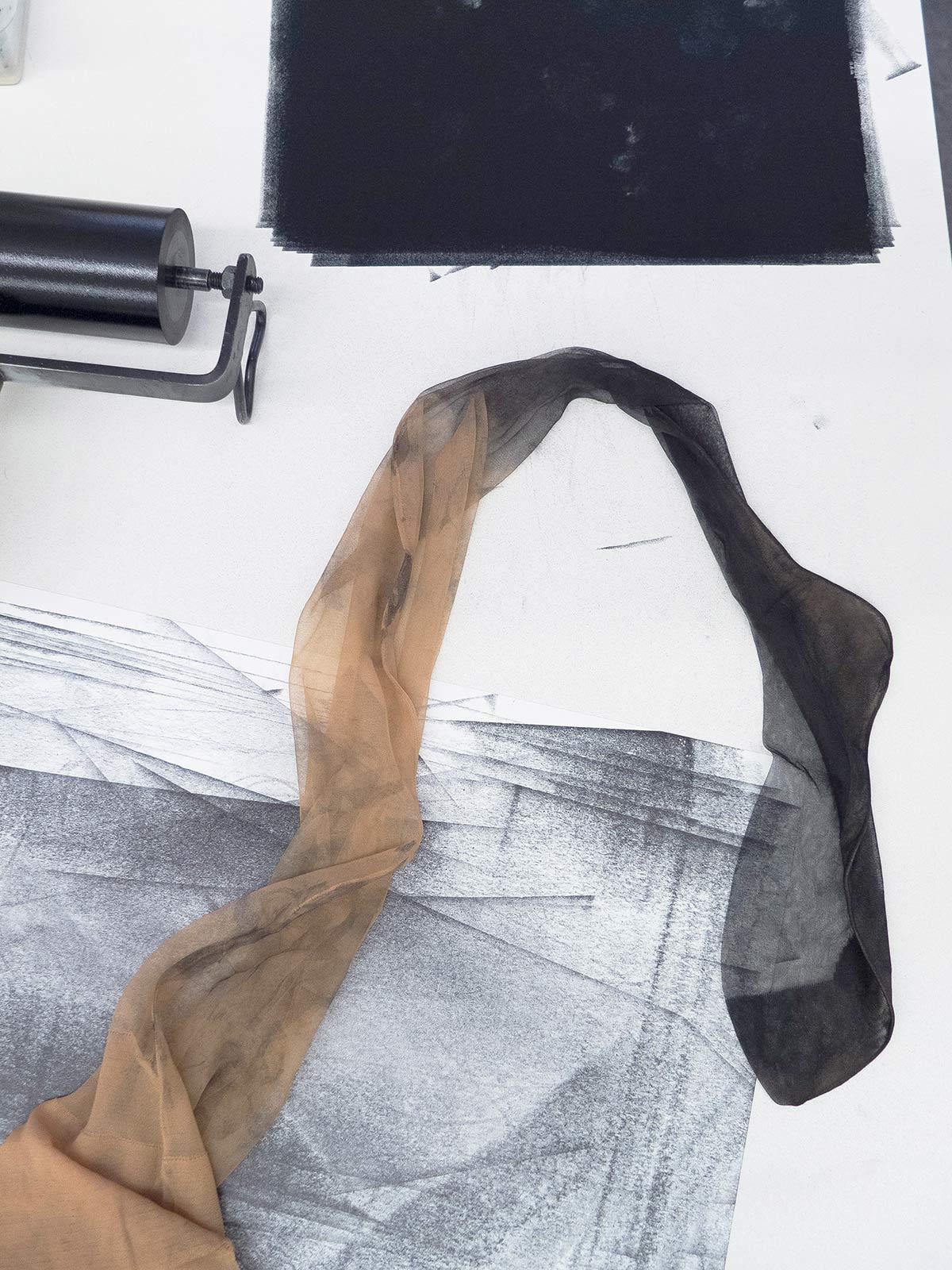 Schwarze Druckfarbe auf einer Arbeitsfläche mit einer Druckwalze und einem eingefärbten Strumpf
