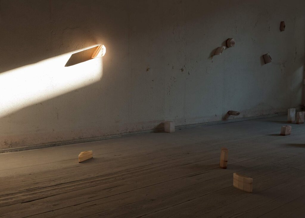 """Installationsansicht """"shaped bodies"""" mit hereinscheinender Abendsonne im ehemaligen jüdischen «Kaufhaus Adolph Totschek»"""