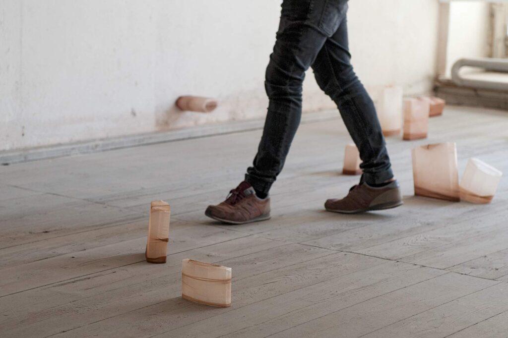 """Eine Person läuft zwischen den Objekten der Installation """"shaped bodies"""""""