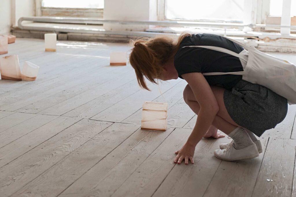 """Eine junge Frau betrachtet ein auf dem Boden stehendes Objekt der Installation """"shaped bodies"""""""