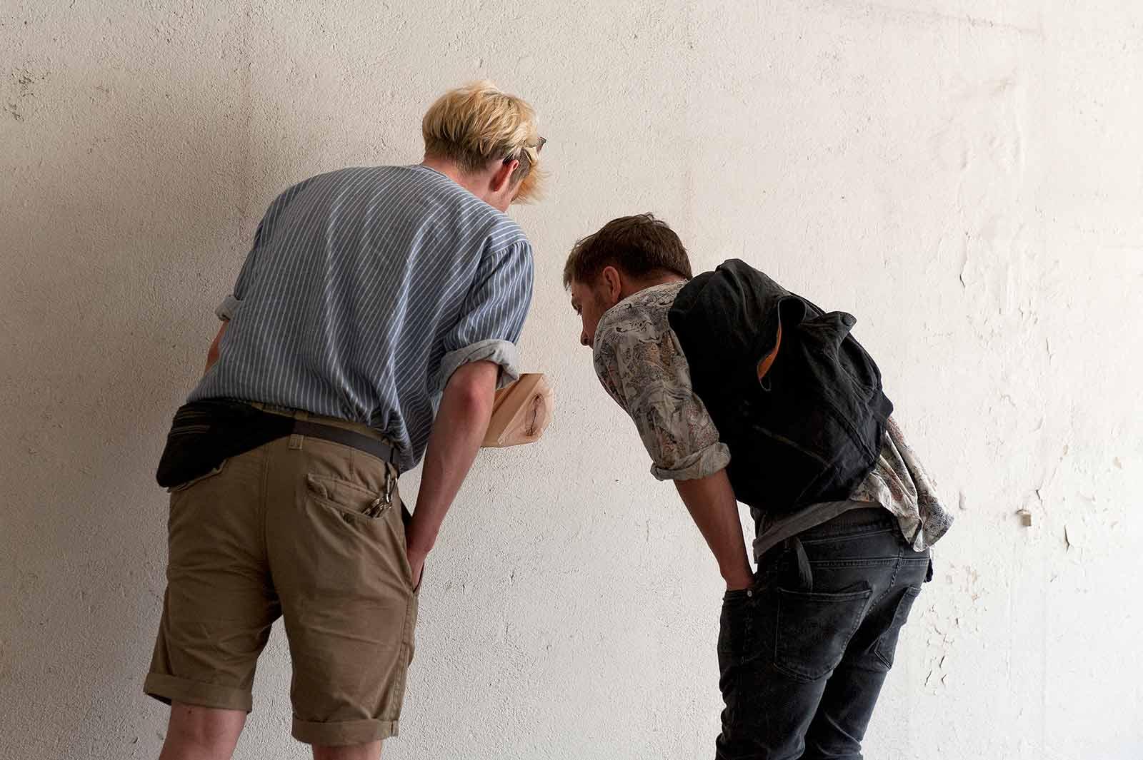 """Zwei junge Männer betrachtet ein an der Wand hängendes Objekt der Installation """"shaped bodies"""""""