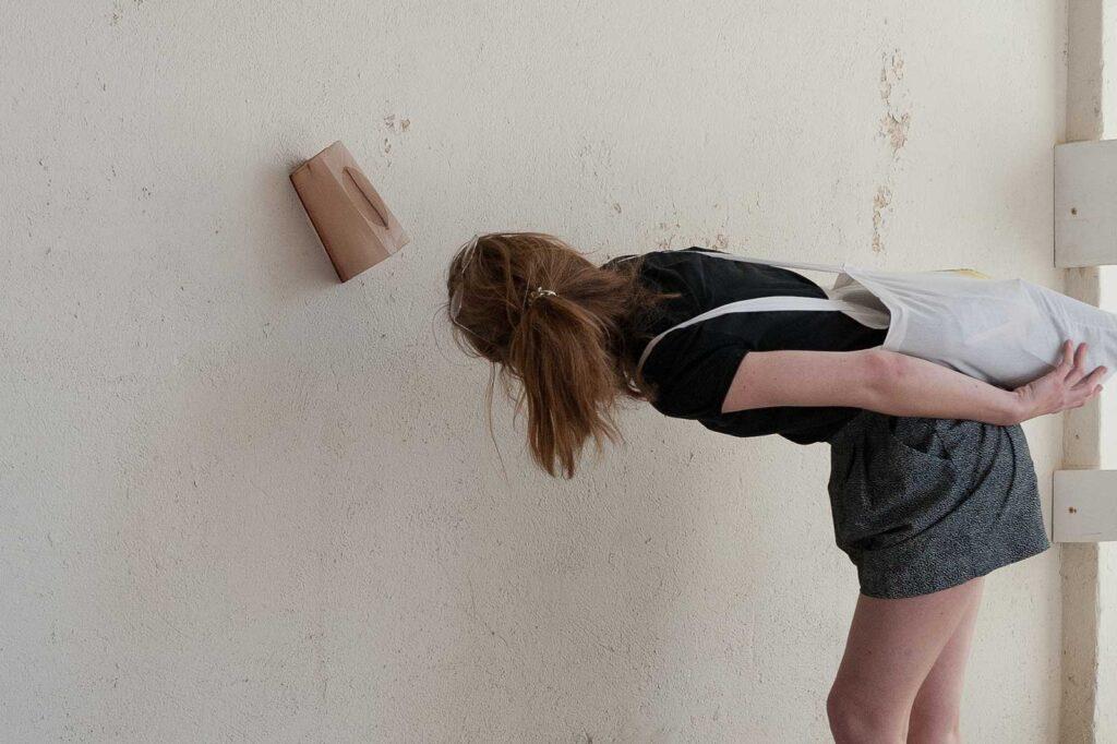 """Eine junge Frau betrachtet ein an der Wand hängendes Objekt der Installation """"shaped bodies"""""""