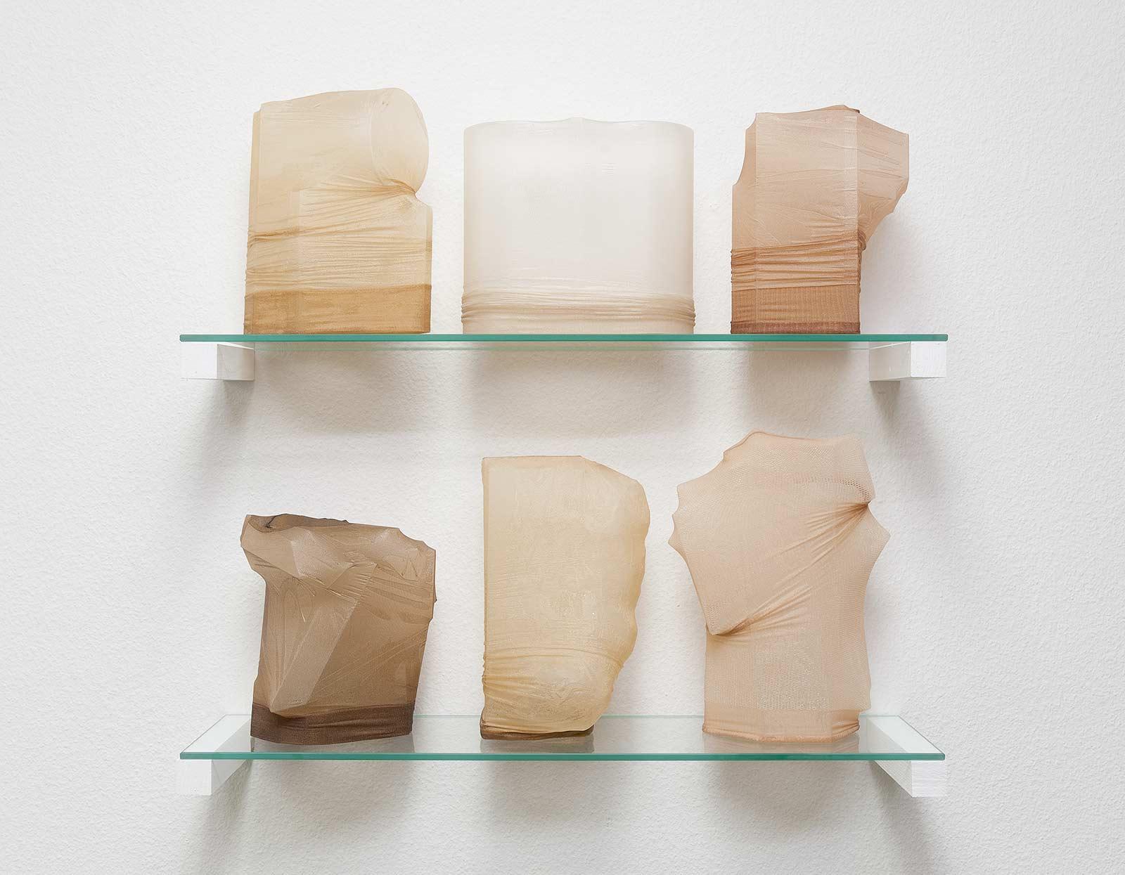 Sechs hohle Objekte aus Polyamid-Strümpfe mit Epoxidharz auf zwei Glastablare