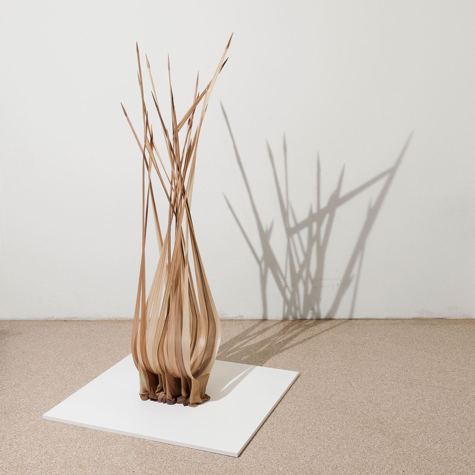 Objekt aus verschiedenen Strumpfhosen in beige und brauntöne mit Epoxidharz, stehend auf einer quadratischen weissen Holzplatte