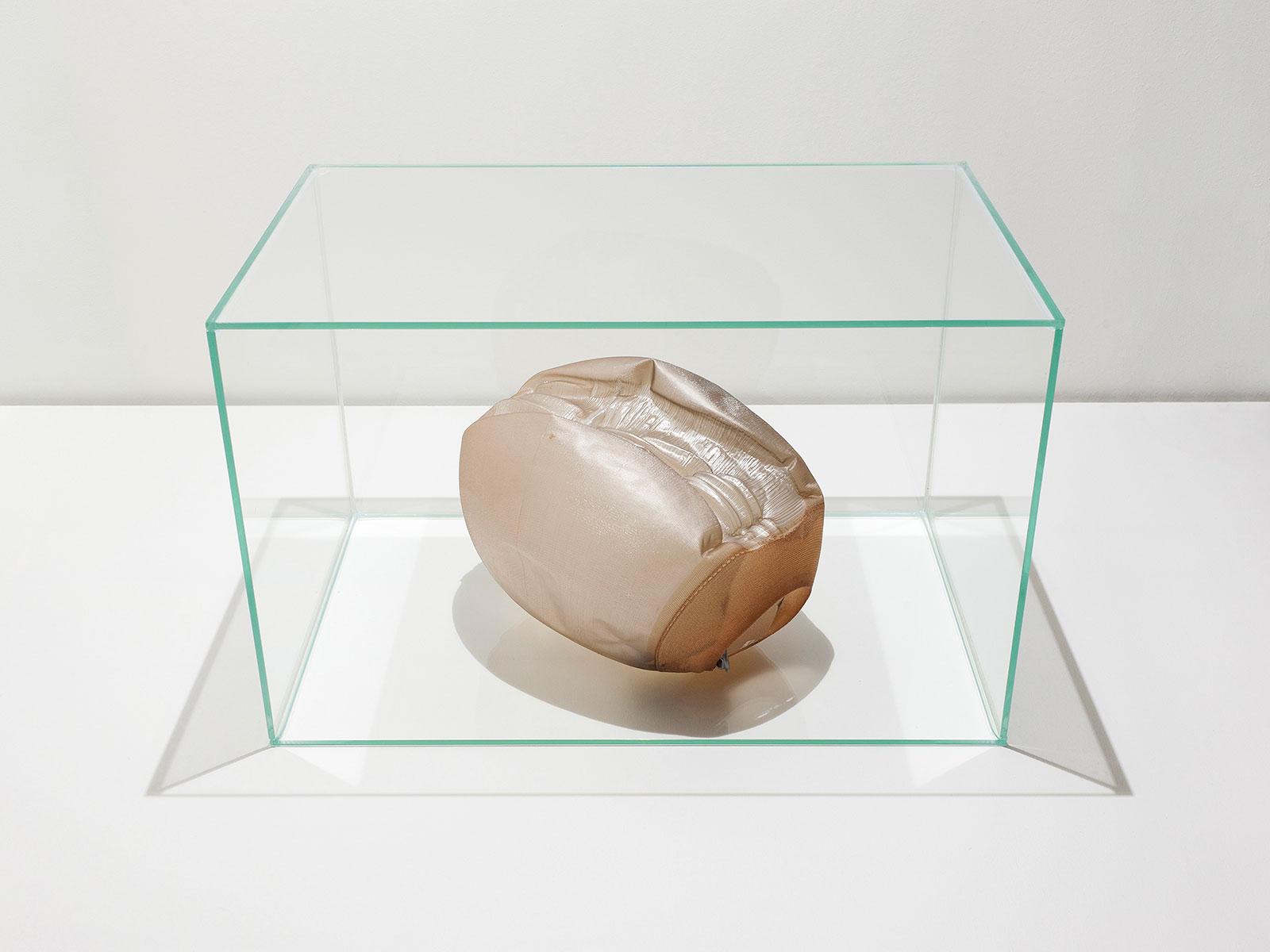 hellbrauner Polyamid-Strumpf mit erschlafftem Ballon und Epoxidharz, platziert in einem Glaskubus