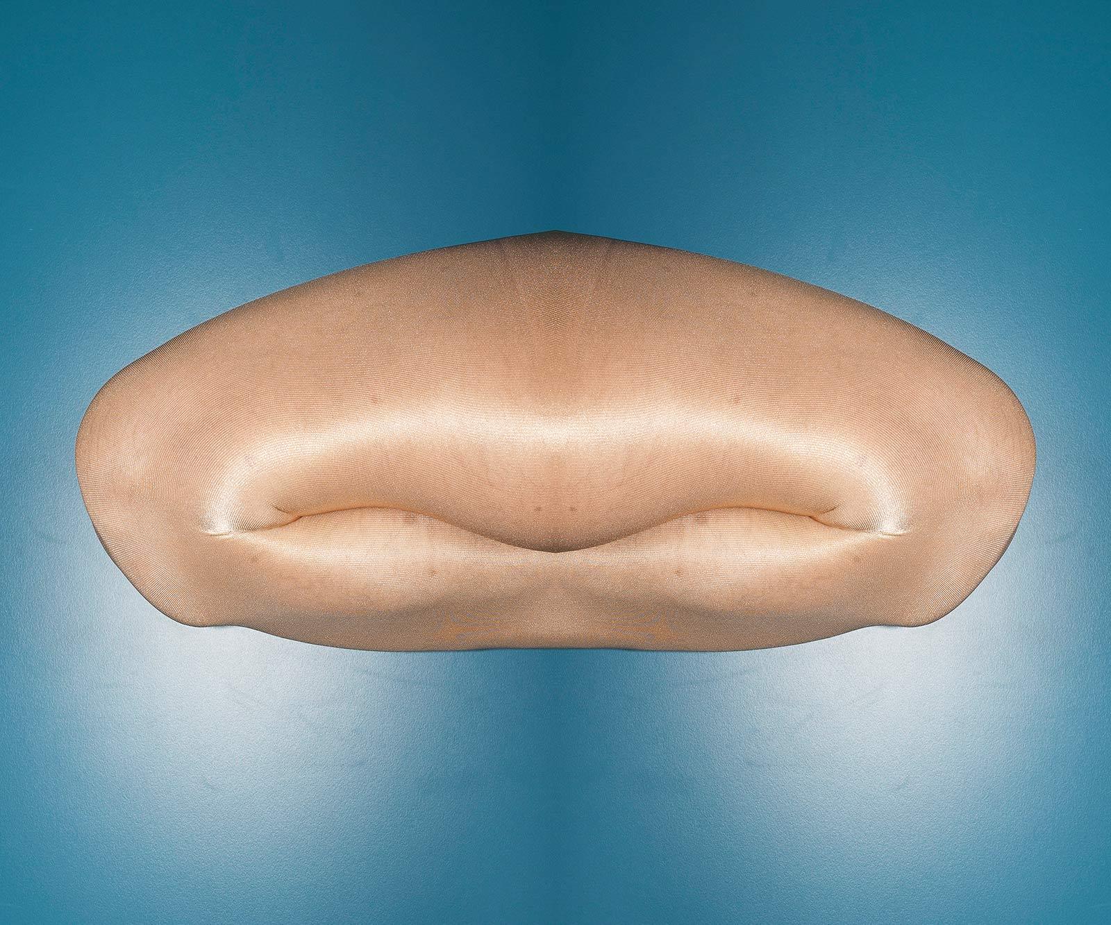 Eine digitale Fotomontage mit einem angezogenen Knie über das ein glänzender Strumpf angezogen ist vor einem blauen Hintergrund