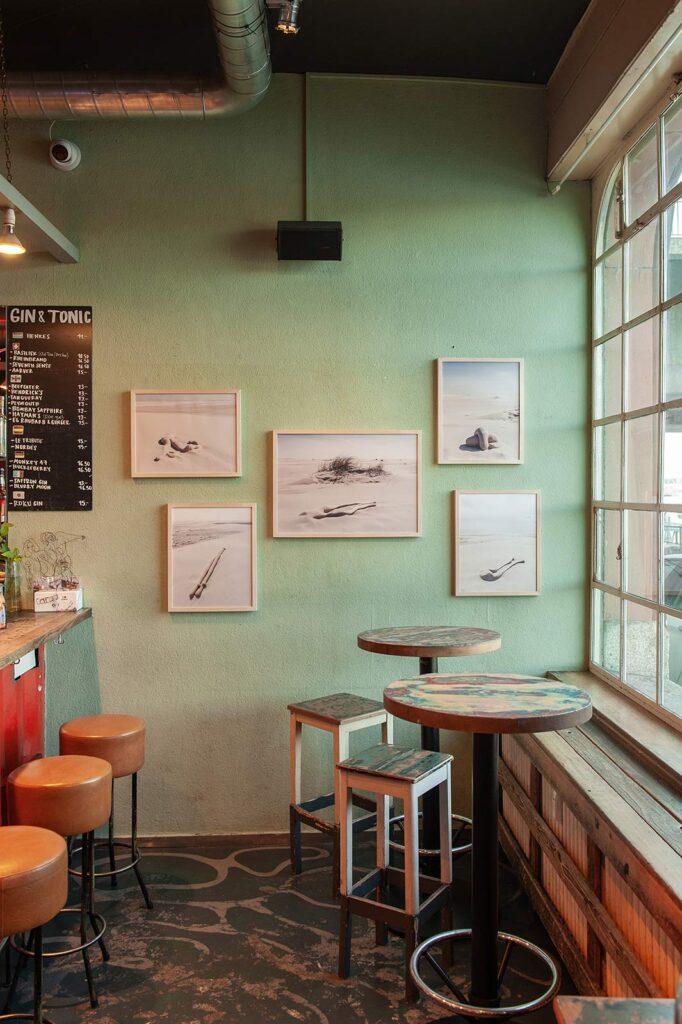 Fünf Bilder der Serie shaped bodies (sand) hängen an einer hellgrünen Wand in der Cargo Bar in Basel anlässlich der Regionale 20