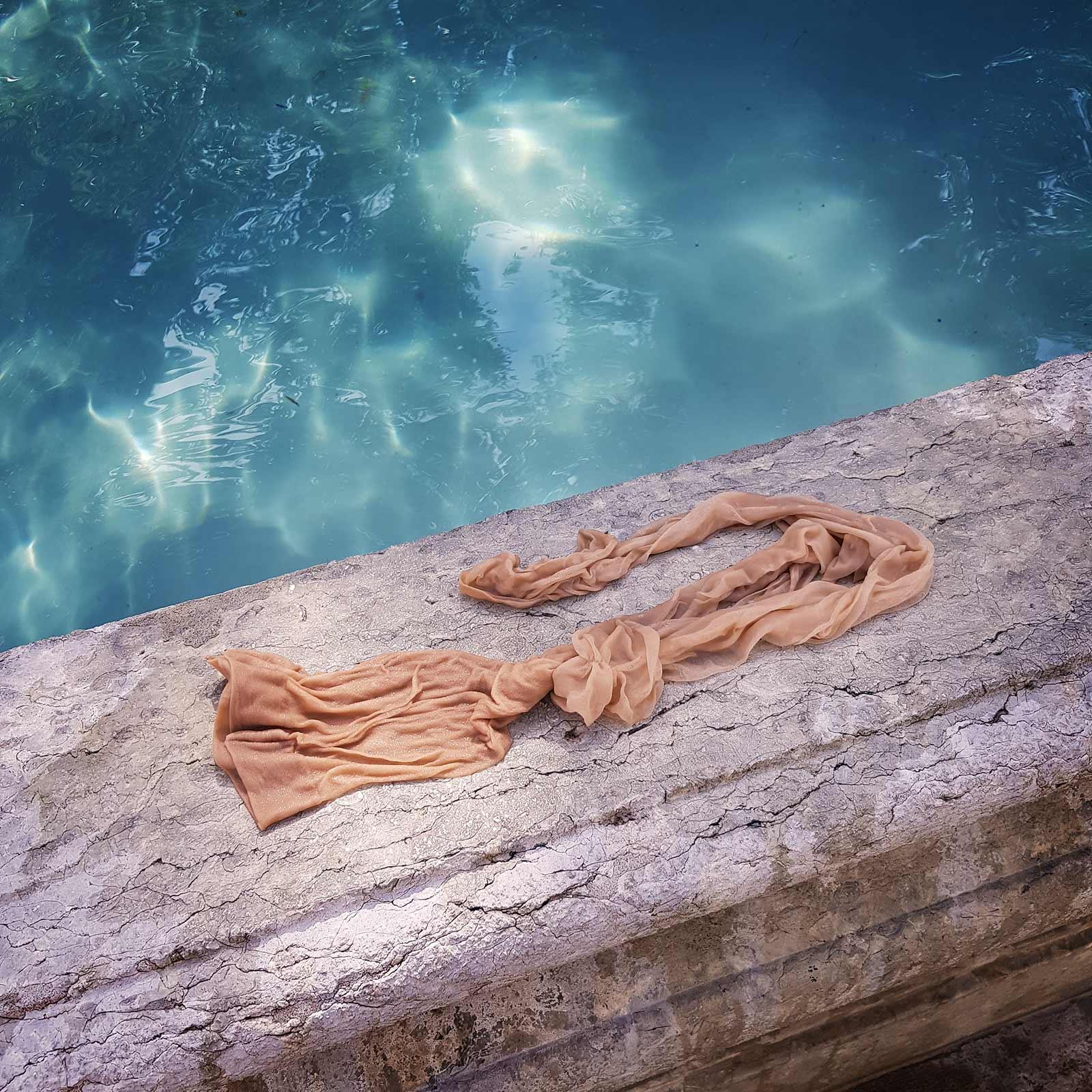 Ein wassergetränkter Strumpf liegt auf dem Brunnenrand und im Hintergrund reflektieren die Sonnenstrahlen im Wasser