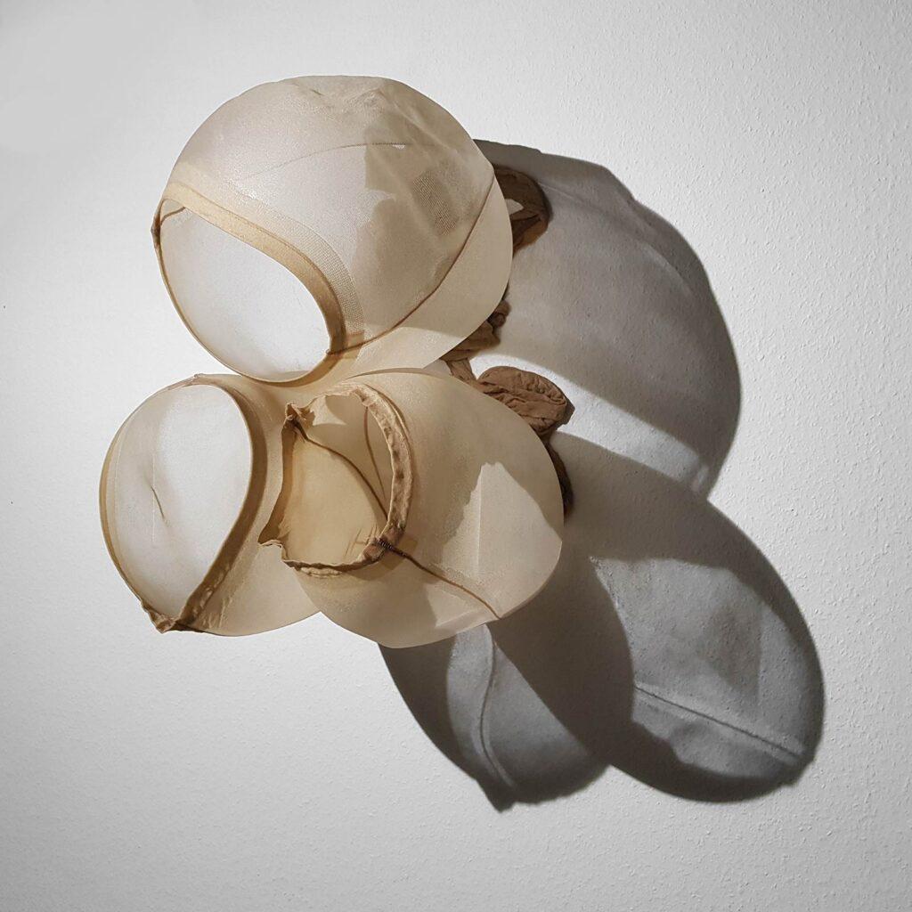 An der Wand hängendes Objekt aus Feisntrumpfhosen und Epoxidharz, das mit einem starken Licht von der Seite beleuchtet wird und dabei ein Schattenbild auf die Wandfläche wirft