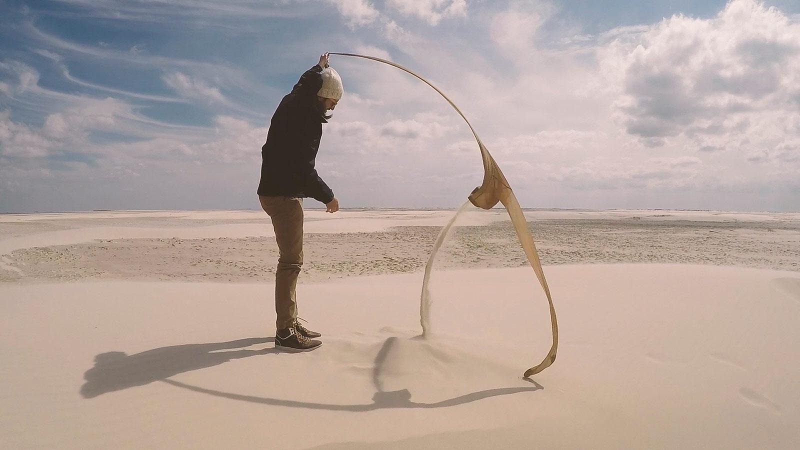 Ein videostill mit dem Künstler Fabian Matz, der ein Strumpf im Wind hält und Sand herausfliesst