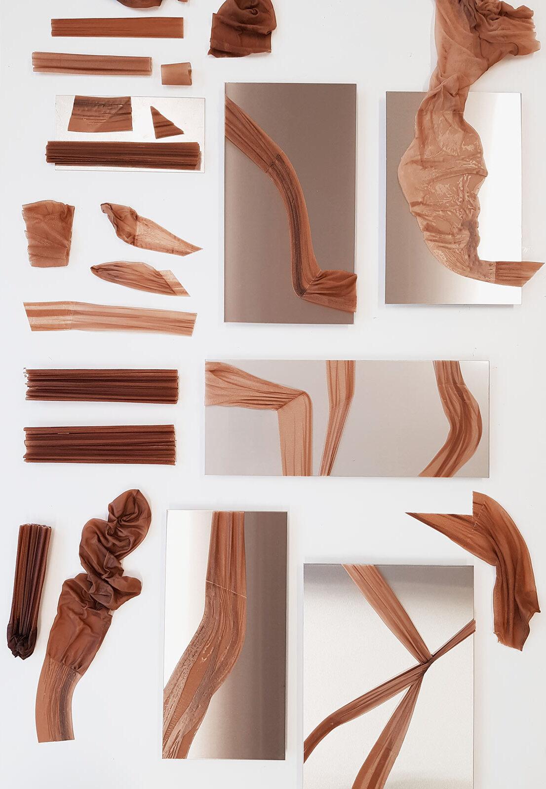 Eine Auslegeordnung im Atelier mit rostfreien Stahlplatten und darauf gelegten zerschnittenen Strumpfstücke mit ausgehärtetem Epoxidharz