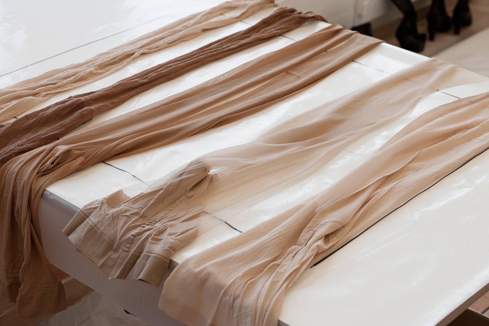 Strümpfe mit verschiedenen Brauntöne und Garnstärken liegen auf dem Arbeitstisch im Atelier