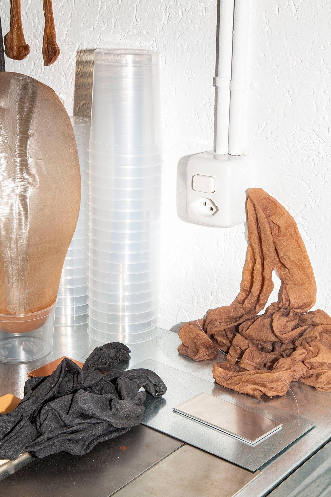 Objekte aus Strümpfe und Epoxidharz mit gestapelten Mischbecher auf einem Regal im Atelier