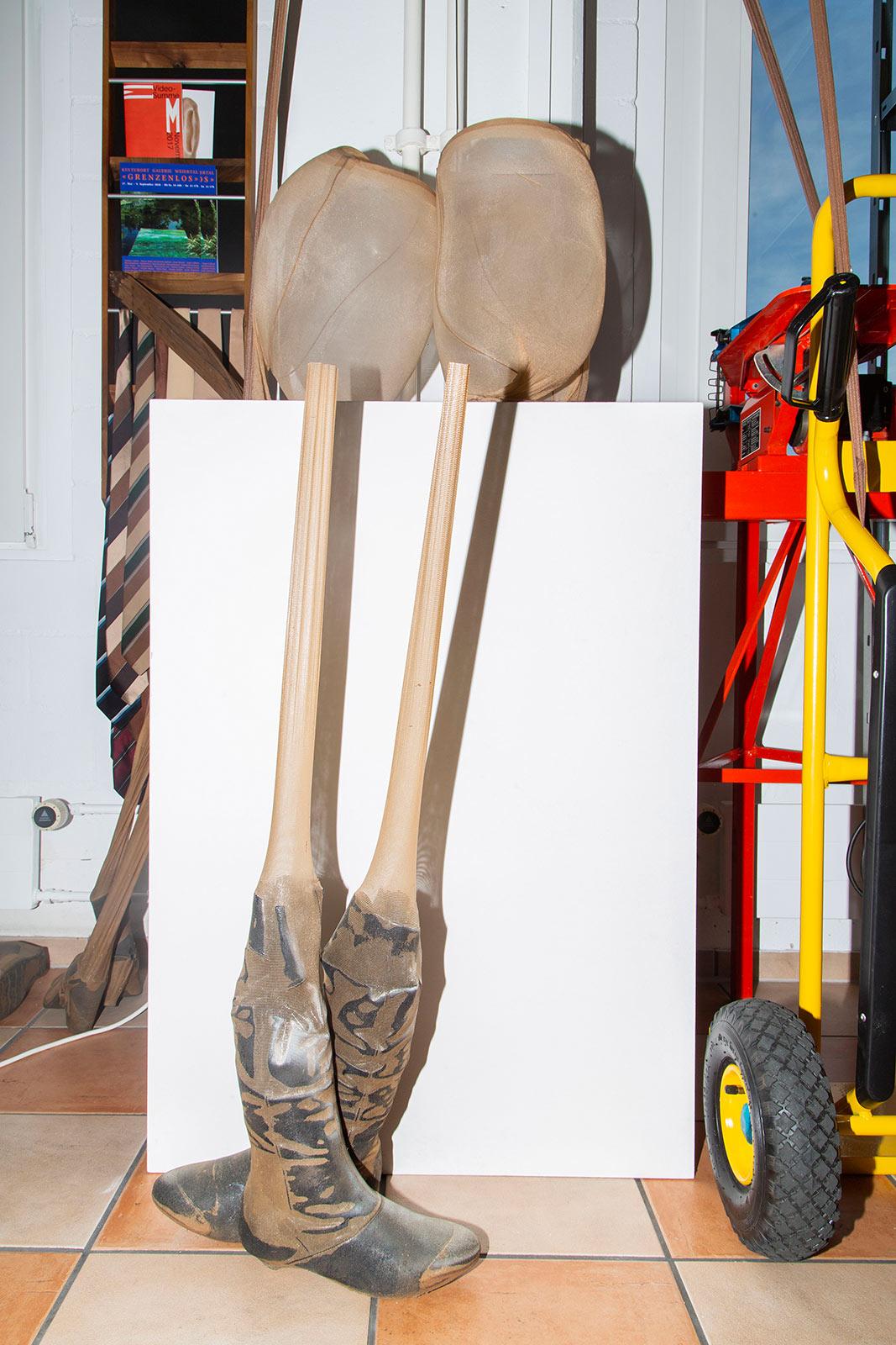 Strumpfobjekt auf einem Sockel mit einem Teilstück aus einer Installation davor mit Stiefeln und einem darübergezogenem Strumpf