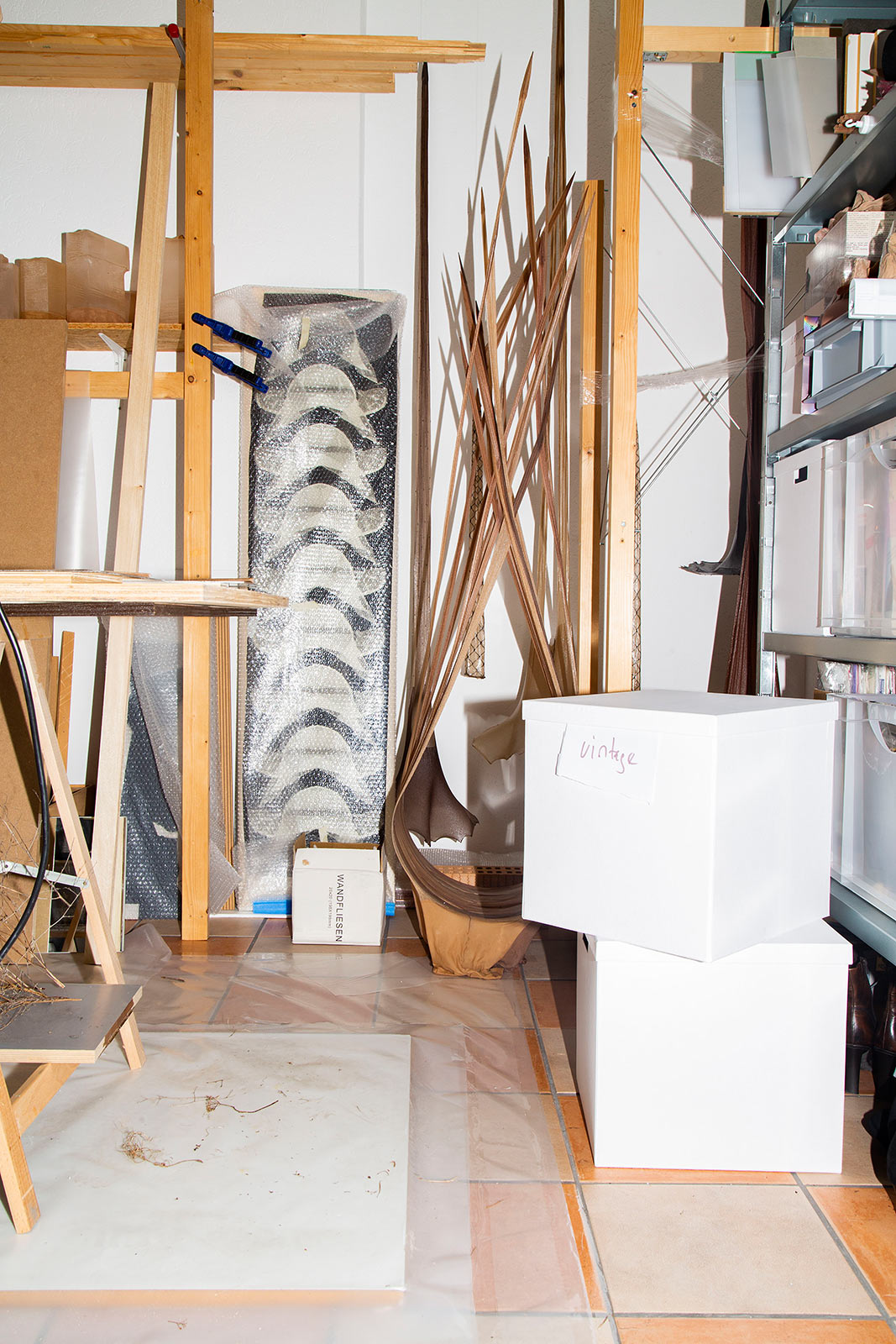 Atelieransicht mit gelagerten Objekten und Kisten mit Strumpfhosen