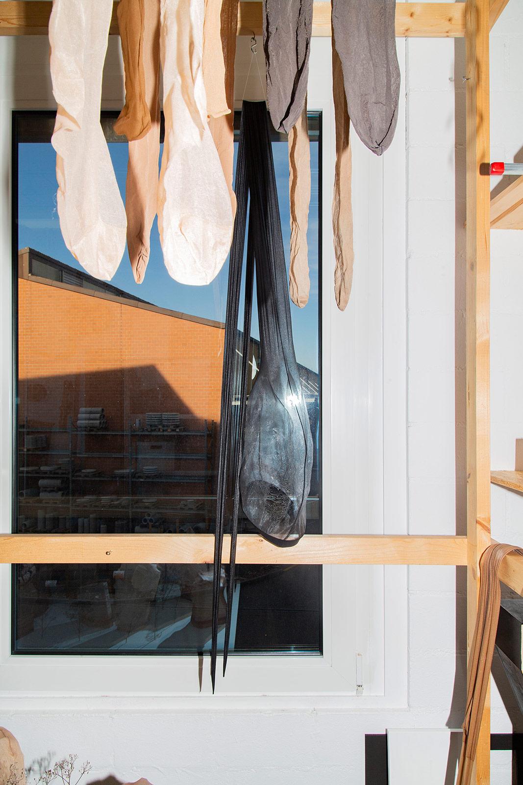 Aufgehängtes schwarzes Strumpfobjekt am Atelierfenster